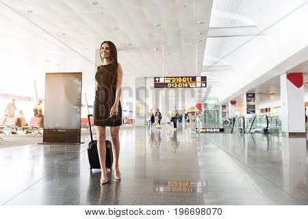 Enjoying travel. Low angle of happy elegant woman with suitcase is going in international airport terminal and looking aside joyfully. Copy space in the right side