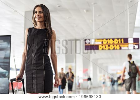 Joyful mood. Portrait of cheerful gorgeous young business woman is standing with handbag at international airport and looking straight ahead with smile. Copy space in the right side