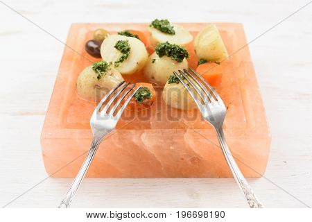 Boiled potatoes and carrots with green chimichurri sauce and vintage forks served on square pink hymalayan salt block closeup