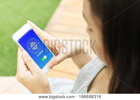 Asian woman hand holding mobile phone and connecting data roaming for calling or use internet
