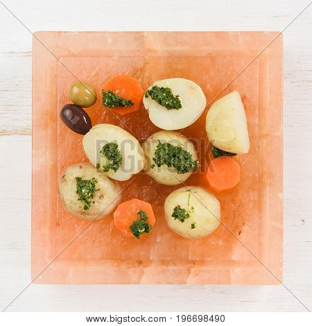Square pink hymalayan salt block with olives boiled potatoes and carrots with green chimichurri sauce top view