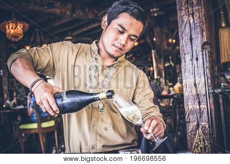 BALI, INDONESIA - JULY 3, 2017: Man pouring champagne in glass. Tropical island Bali