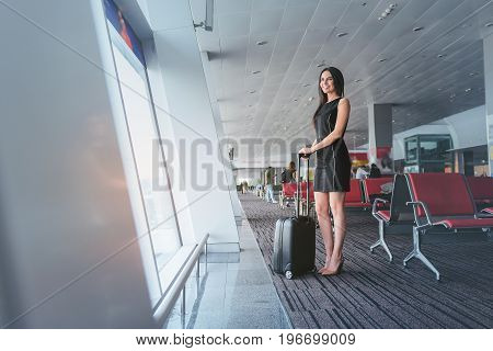 Ready to discover. Charming elegant girl is standing with suitcase and looking at airplanes through airport window while expressing gladness. Copy space in left side