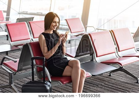 Sunny day. Stylish cheerful woman is reading news on smartphone while sitting on red bench in waiting hall at international airport against big window. Copy space in the right side