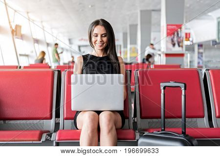 Full of inspiration. Happy gorgeous brunette woman is working on laptop while sitting on bench in waiting hall at airport and expressing gladness
