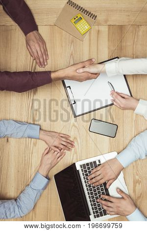 Top View Of Businesspeople Shaking Hands On Meeting With Documents And Laptop At Workplace
