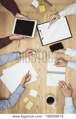 Top View Of Businesspeople On Meeting With Documents And Digital Tablet At Workplace
