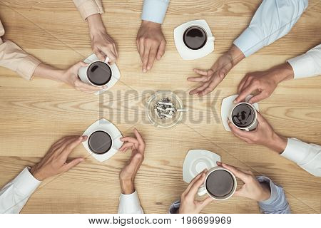 Top View Of Businesspeople Smoking On Coffee Break On Wooden Tabletop