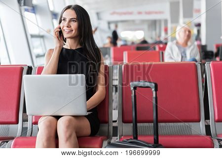 Busy lady. Joyful and elegant businesswoman is sitting at waiting hall in airport with suitcase and laptop and talking on her smartphone while looking aside with smile. Copy space in the right side