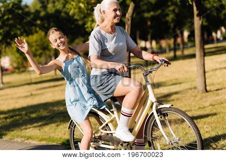 Catch the wind. Overjoyed pretty girl sitting on the back sit of the bicycle while her grandmother riding it