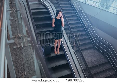 Keeping in touch. Top view of glamorous positive businesswoman is having pleasant conversation while getting down on escalator at airport with her baggage