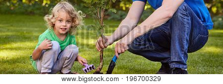 Focused Boy Gardening With Man