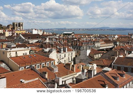Panoramic view over the red roofs of the ancient Lisbon city with Se Cathedral and the tagus river on the background