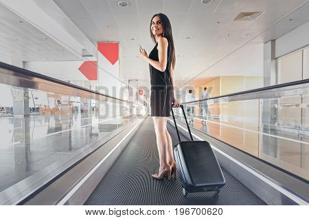Full of joy. Low angle of cheerful graceful business woman is standing on moving walkway at international airport and holding smartphone and suitcase. She is turning back with smile