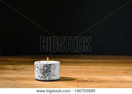 Tealight or candle with flame inside a holder. Placed on the kitchen table at home. Copy space with room for your own text or message.