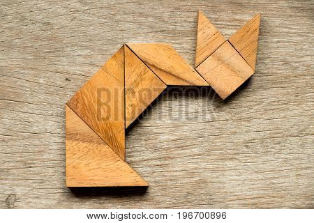 Tangram puzzle in cat sitting shape on wood background