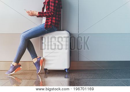 Free WiFi zone. Vigorous young female tourist is sharing news using smartphone while sitting on white suitcase in international airport. Copy space in the right side