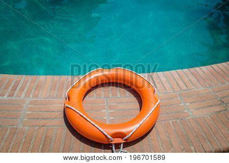 Orange lifebuoy or ring buoy on edge of swimming pool outdoors