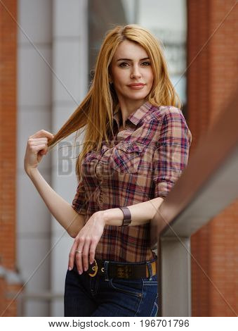 Portrait of a cute red-haired girl in a plaid shirt, pulling her hair.
