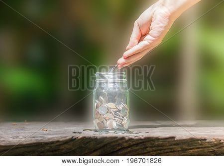 Hand drops money into a glass jar for a savings on the wooden table  with blurred background