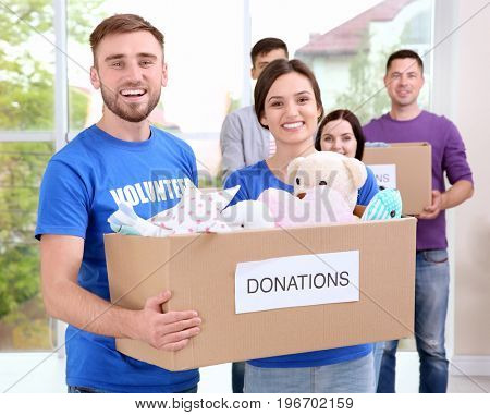 Young volunteers with box of donations indoors
