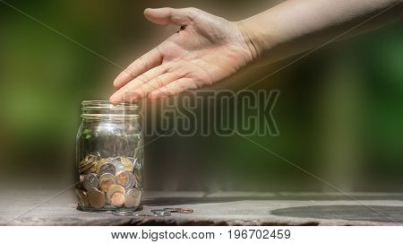 Hand point a glass jar for a savings on the wooden table  with blurred background