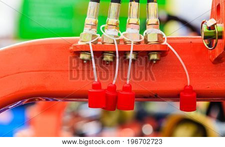 Agriculture equipment concept. Four hydraulic pneumatic pipes on red machinery with plugs
