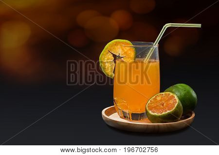 Orange juice with tangerine in wooden tray on bokeh background