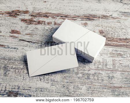 Blank white business cards on vintage wood background. Template for design portfolios. Responsive design mock up.