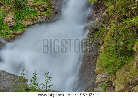 an imposing waterfall falls impetuous from the glaciers in the National Park of Great Paradisein Piedmont ,Italy