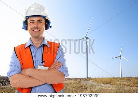Engineer and wind turbines on background