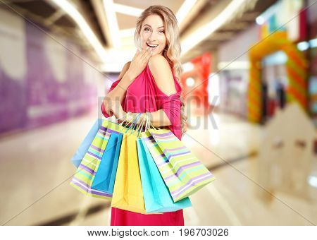 Young woman with shopping bags at store. Boxing Day concept
