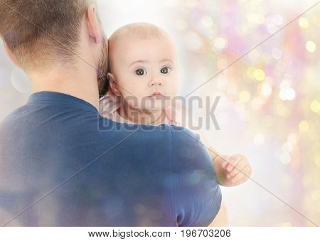 Father with baby on Christmas lights background