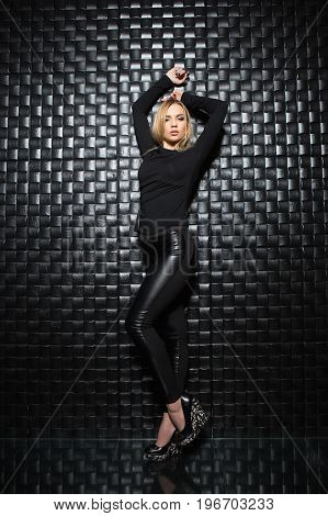Alluring young woman wearing black clothes posing in studio