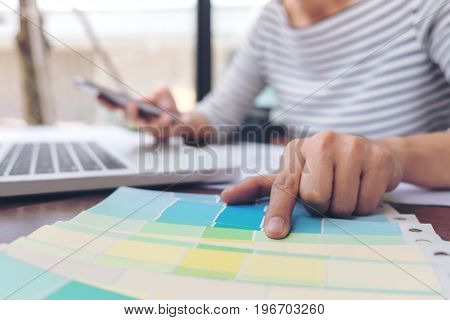 Creative creativity graphic designer working with graphics tabletlaptop and smart phone colour chart at workplace on wooden desk colour ideas style concept.