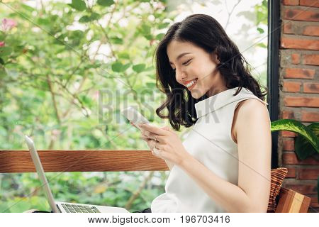 Confident Young Asian Woman In Smart Casual Wear Typing On Phone.