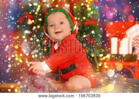 Cute baby in costume of Santa's helper and Christmas tree on background. Holidays celebration concept