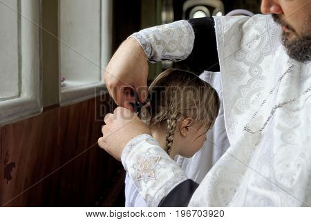 The baptism of a child in the Orthodox Church. Hair cut during the sacrament of baptism. The priest cuts off a strand of hair from the girl during baptism.