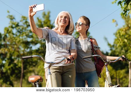 Just smile. Cheerful delighted senior woman holding phone and making selfies with her granddaughter while resting after riding bicycles