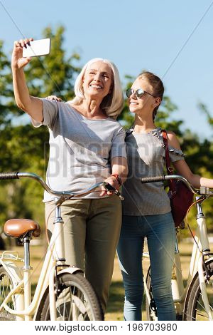 More photos. Delighted smiling senior woman making selfies with her granddaughter while holding bicycles and standing in the park