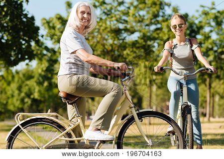 True friends. Cheerul delighted senior woman riding bicycle with her granddaughter in the park while enjoying sunny weather and spending time with pleasure