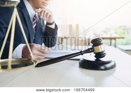 Close up of gavel Male lawyer working with scales of justice book report the case on wooden table in office Law and justice concept.