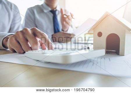 Man sign a home insurance policy on home loans Agent holds loan investment chart graph documents and calculating table installment payment Real Estate concept.