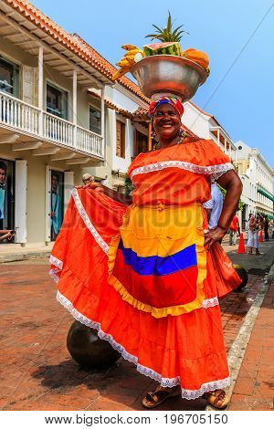 Cartagena, Colombia - March 19, 2016: Woman in traditional costume selling fruit in the historic city of Cartagena de Indias in Colombia.