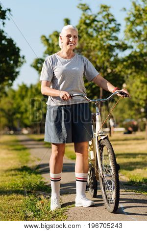 Sport every day. Contented smiling senior woman standing near her bicycle in the park while going to have a ride