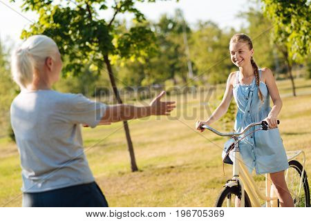 Have not seen you for a long time. Cheerful delighted girl riding a bicycle while approaching her grandmother