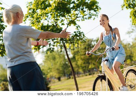 Ride to me. Cheerful little girl riding a bicycle in front of her grandmother while resting together in the park