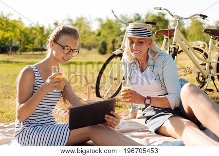 What is news. Cheerful delighted girl and her grandmother sitting on the blanket and enjoying picnic while using a tablet