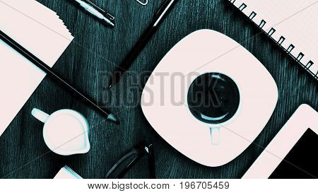Coffee Break Concept with Stationery Items Coffee Cup with Milk Jug Digital Tablet and Greens Eyeglasses closeup on Wooden background. Turquoise toned