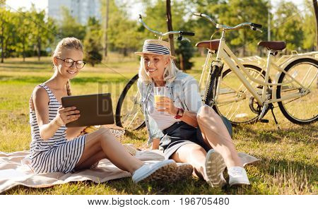 Best way to spend time. Cheerful delighted senior woman having a picnic with her granddaughter and using tablet while spending weekend together